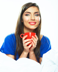 Woman in pajamas loungewear sitting with red coffee cup