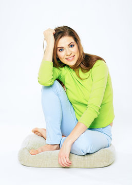 Smiling woman casual dressed sitting on a floor.