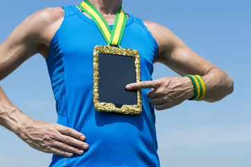 Athlete using tablet hanging as gold medal against blue sky