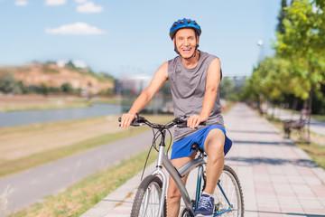 Cheerful senior biker posing on a sidewalk