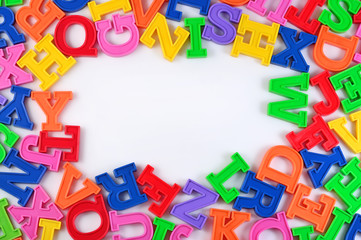 Frame of plastic colorful alphabet letters on a white