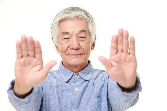 senior Japanese man making stop gesture
