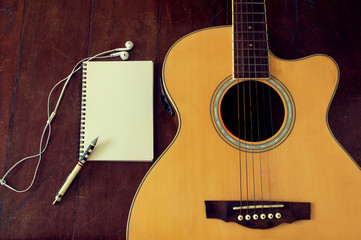 Notebook and wooden pencil on guitar