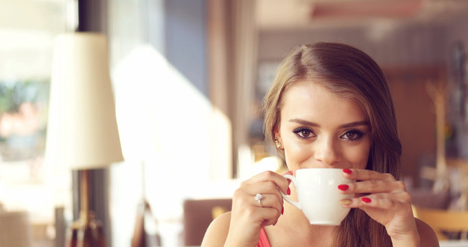 Smiling Young Woman Drinking Coffee in Sunny Cafe