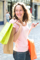 Young attractive woman using mobile during shopping