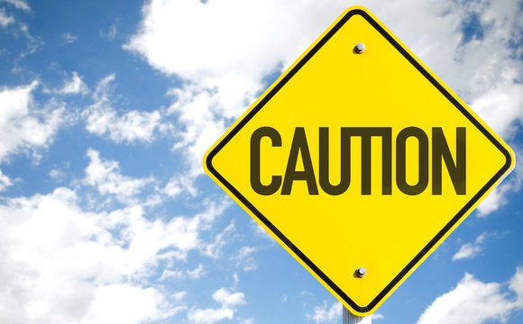 Caution sign with sky background