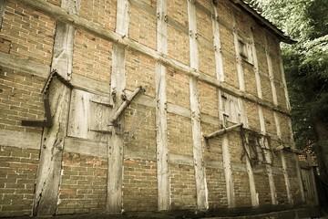 Alte Ackerbaugeräte von früher an einer alten Fachwerkfassade aufgehängt