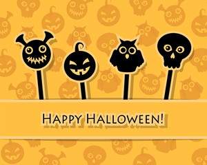 Paper Halloween symbols on sticks on an orange background