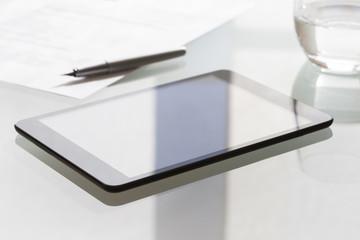 Digital tablet on modern glass table in office