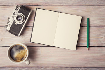 Retro camera, open memo book and cup of coffee on rustic wooden