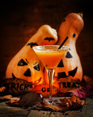 Orange Halloween cocktail and holiday pumpkins on a dark mystica