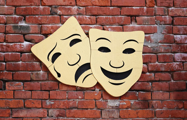 Comedy and tragedy theater masks on old vintage brick wall