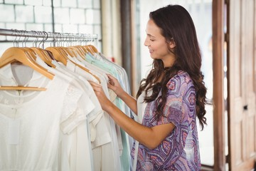 Smiling woman looking at clothes rack
