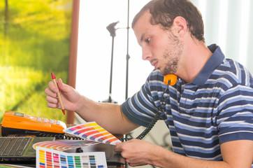 Man wearing blue white striped t-shirt sitting by work desk