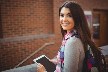 Portrait of pretty student holding tablet