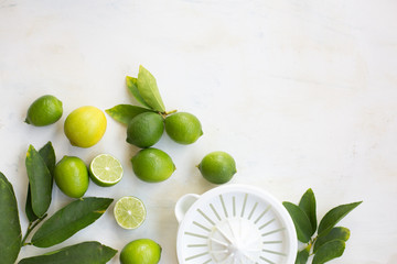 limes and a juicer on a white table