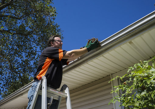 Worker Cleaning Gutters