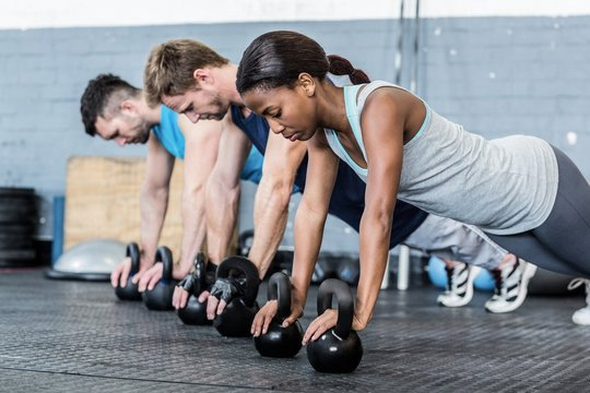 Young athletes doing push ups with kettlebells in gym