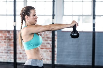 A fit woman lifting kettlebell