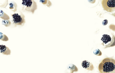 Frame from bluberries and blackberries falling into creamy milk