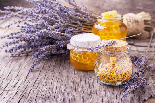 Arrangement of small glass jars with lavender honey, honeycombs and bee pollen