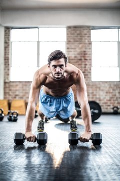 Muscular man doing push ups with dumbbells
