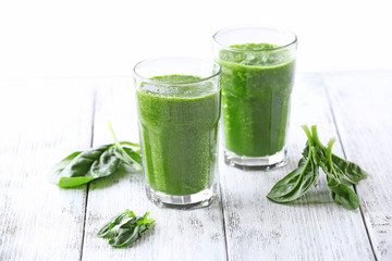 Glasses of spinach juice on wooden table, closeup