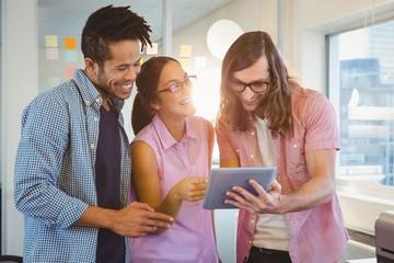Happy creative business people looking at digital tablet