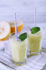 Glasses of melon cocktail on white wooden background