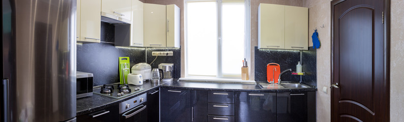 panoramic view of kitchen with appliances and utensils