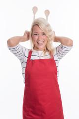 Hausfrau hält sich Kochlöffel hinter den Kopf