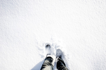 Looking down on feet in white snow during hike