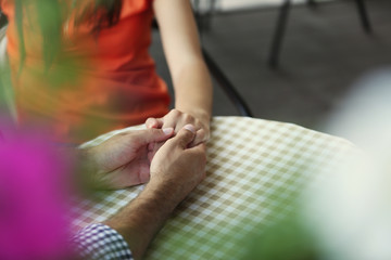 Loving couple holding hands on table in cafe