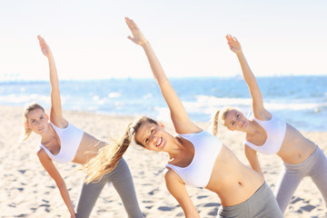 Group of women practising yoga on the beach