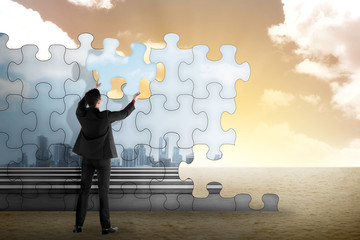 Business person building puzzle of city in the desert