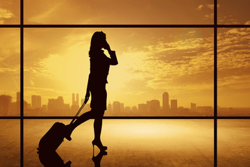 Silhouette of business woman walking with suitcase