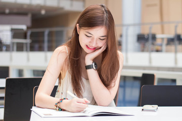 Portrait of thai adult beautiful girl write a book sitting in university.