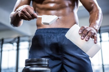 Fit shirtless man scooping protein powder