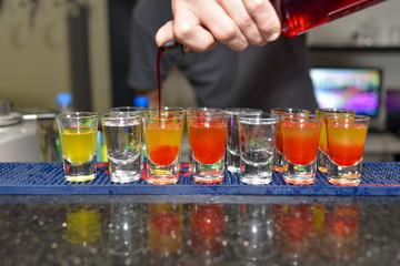 Barmen pouring colorful shots