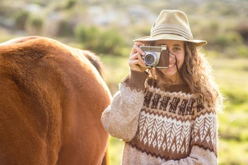 Young woman with her horse taking photo