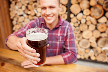 Cheerful man is swigging lager in pub