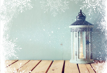 white wooden vintage lantern with burning candle and tree branches on wooden table. retro filtered image with glitter and snowflake overlay