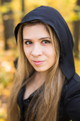 portrait of beautiful blond young woman in forest. Halloween day