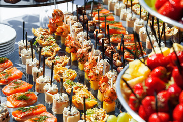 Photo sur Toile Buffet, Bar meat, fish, vegetable canapés on a festive wedding table outdoor