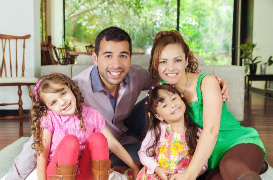 Beautiful hispanic family of four sitting on floor in livingroom