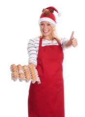 Weihnachtsfrau mit rohen Eiern zeigt Daumen hoch