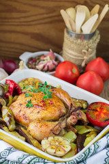 Baked chicken with vegetables. Dinner in a rustic style