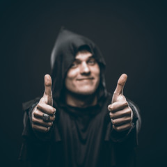 guy in a black robe showing thumbs up