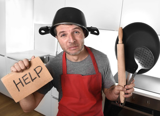 funny man holding pan with pot on head in apron at kitchen asking for help