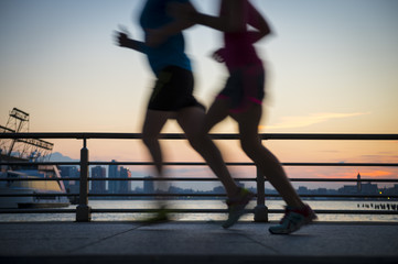 Motion blur silhouettes of joggers running at sunset on the Hudson River boardwalk in New York City